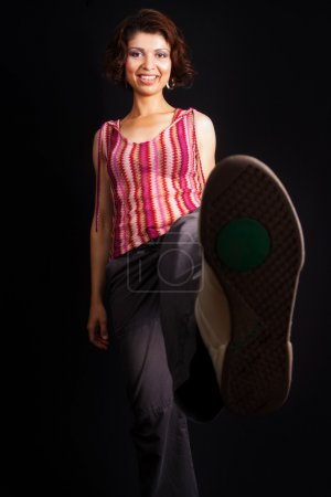 Photo for Woman kicking and showing her sport shoe sole - Royalty Free Image