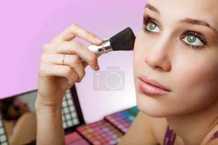 Makeup and cosmetics - woman using blush brush