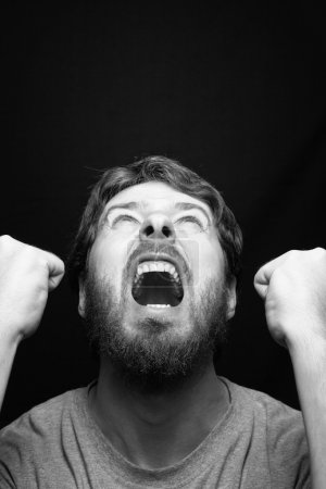 Photo for Scream of angry rebel man over black - Royalty Free Image