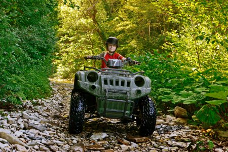 A little boy wearing a helmet riding a quad bike on the shore of a mountain river.