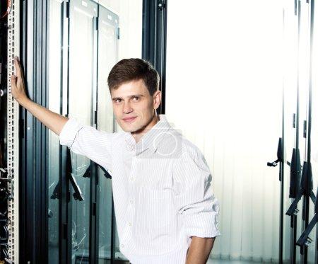 Photo pour L'ingénieur en costume se tiennent dans le datacenter près de matériel télécom et souriant. copie-espace. - image libre de droit