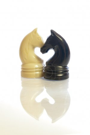 Black and white chess horses shaping a heart