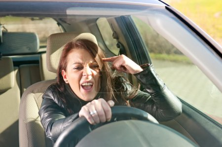 Angry young woman gesturing in the car...