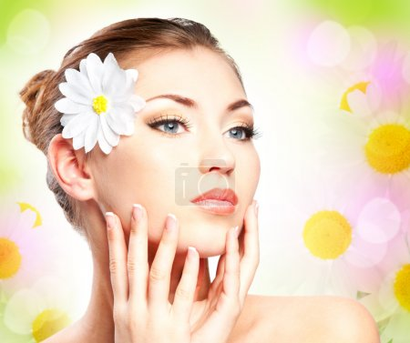 Photo for Spa (spring) beautiful girl with camomile touching her face - Royalty Free Image