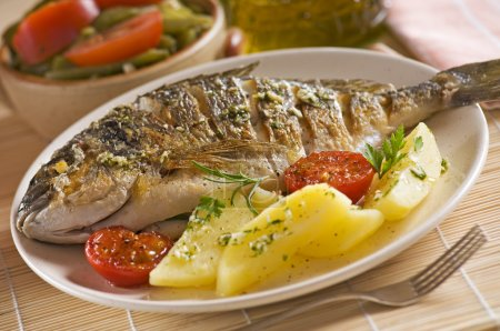Photo for Roasted gilt fish with potatoes and (garlic, parsley) sauce - Royalty Free Image