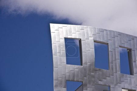 Foto de Cielo azul brilla a través de las ventanas abiertas en la fachada de un edificio de acero - Imagen libre de derechos