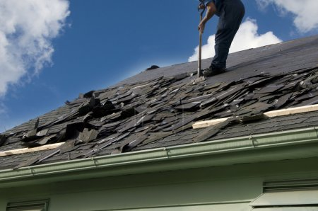 Photo for Removing old shingles to prepare a roof for a new installation with blue sky - Royalty Free Image