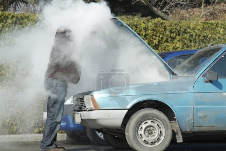 Photo for Man looking at a smoking engine in his car - Royalty Free Image