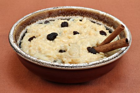 Large bowl of creamy rice pudding with raisins and cinnaomon sti