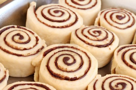 Photo for A pan of raw, homemade cinnamon buns in a pan ready to bake. Selective focus. - Royalty Free Image
