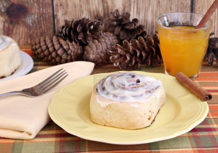 Photo for Fresh cinnamon bun with a glass of apple cider and cinnamon sticks. - Royalty Free Image