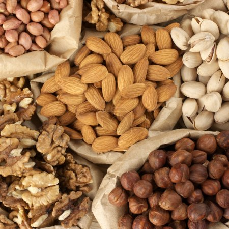 Photo for Close-up of assorted nuts in paper bags. Top view point. - Royalty Free Image
