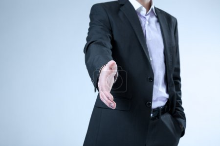 Businessman stretches out hand for handshake. Hello, welcome, offer, contract, agreement etc. classic business concept. No head, no face on the shot