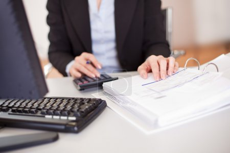 Photo for Closeup of a businesswoman doing finances in the office - Royalty Free Image