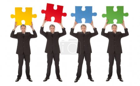 Photo for Group of business holding jigsaw puzzle. Isolated on white - Royalty Free Image