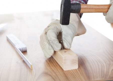 Worker hammering a nail into piece of wood