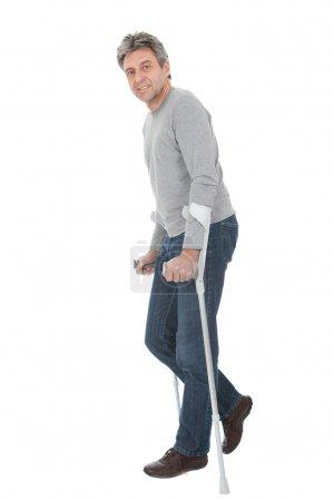 Photo for Senior man walking using crutches. Isolated on white - Royalty Free Image