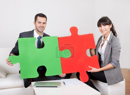 Photo for Two business connecting puzzle pieces at the office. Teamwork concept - Royalty Free Image