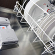 Open dishwasher with clean plates in it, focus on ...