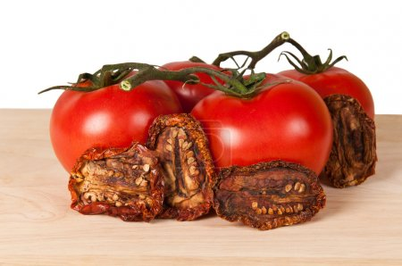 Photo for Fresh and dried tomatoes on a wooden board - Royalty Free Image