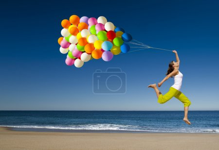 Photo for Beautiful and athletic girl with colorful balloons jumping on the beach - Royalty Free Image