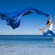 Beautiful young woman jumping on the beach with a ...