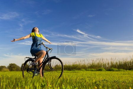 Photo for Happy girl over a bicycle and looking the view, in a green meadow - Royalty Free Image