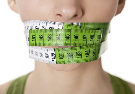 Photo for Portrait of a young woman with a green measuring tape covering the mouth - Royalty Free Image