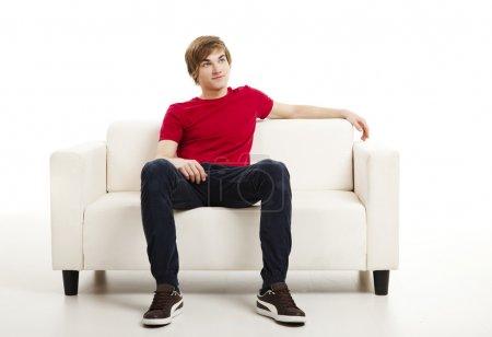 Foto de Joven guapo en casa sentado en el sofá - Imagen libre de derechos