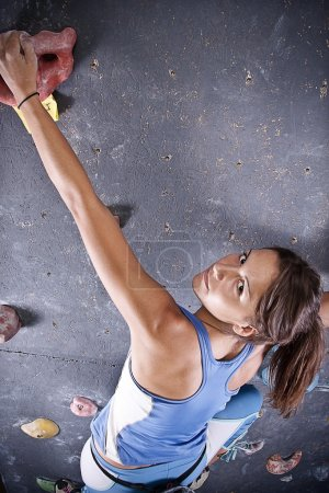 Photo for Pretty, young, athletic girl climbing on an indoor rock-climbing wall - Royalty Free Image
