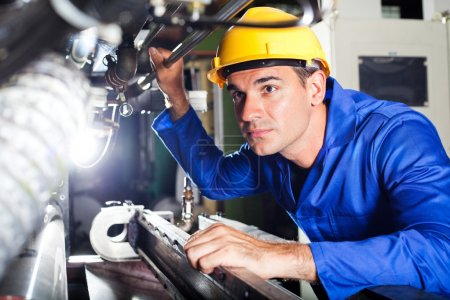 Modern machine operator working in factory...