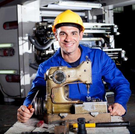 Foto de Feliz mecánico reparación de la máquina de coser industrial en fábrica - Imagen libre de derechos