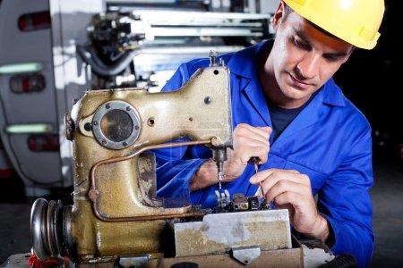 Photo pour Mécanicien masculin réparant la machine à coudre industrielle en usine - image libre de droit