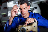 Mechanic repairing industrial sewing machine