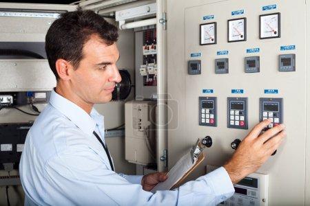 Industrial engineer adjusting machine settings
