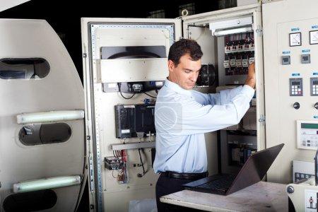 Technician repairing computerized machine