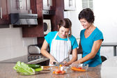 Mother teaching teenage daughter cooking