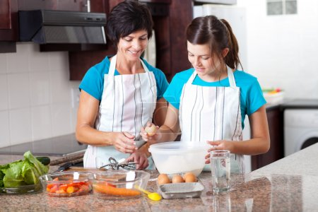 Photo for Middle aged mother teaching teen daughter baking in kitchen - Royalty Free Image