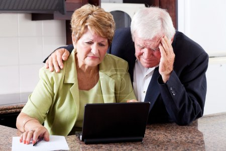 Unhappy senior couple worrying about expenses