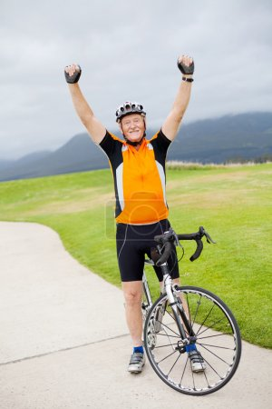 Photo for Cheerful active senior man on bicycle with arms up - Royalty Free Image
