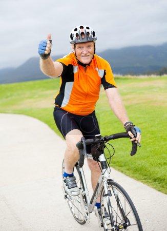 Photo pour Heureux senior mâle bicycliste donnant pouce sur vélo - image libre de droit