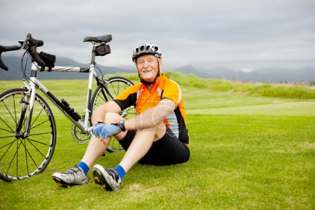 Photo for Happy senior cyclist sitting on grass resting - Royalty Free Image