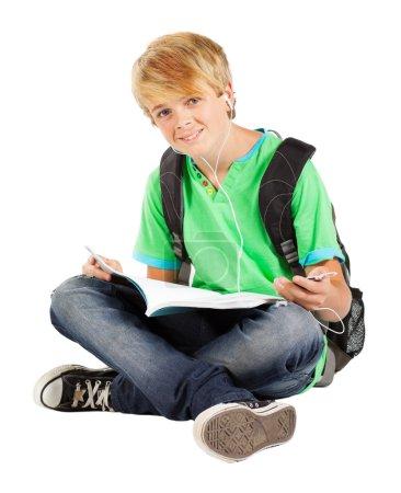 Foto de Muchacho adolescente sentado en piso leyendo libro aislado en blanco - Imagen libre de derechos
