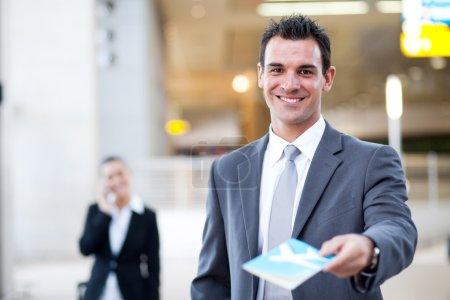 Photo pour Homme d'affaires remettant le billet d'avion au comptoir d'enregistrement de l'aéroport , - image libre de droit