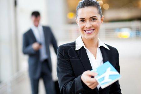 Photo pour Femme d'affaires attrayante remise de billets d'avion au comptoir d'enregistrement de l'aéroport - image libre de droit