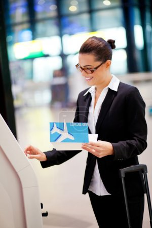 Businesswoman using self help check in machine at airport