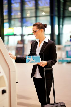 Businesswoman using self help check in machine