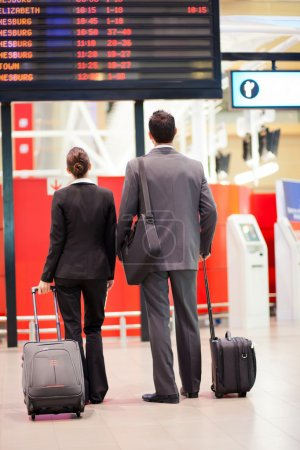 Business travellers looking at airport information board