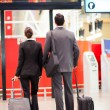 Two business travellers looking at airport informa...