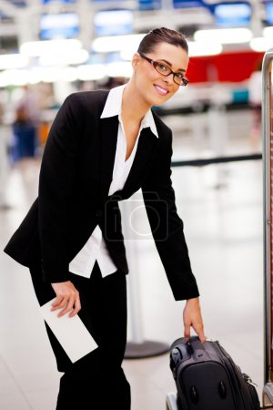 Businesswoman checking size of carry-on luggage